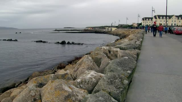 Remnants of Hurricane Ophelia heads towards the UK and Ireland IRELAND Galway EXT People walking along seafront road Man jumping from diving board...