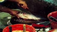 Entfernen von Fischschuppen in einen Fischmarkt,