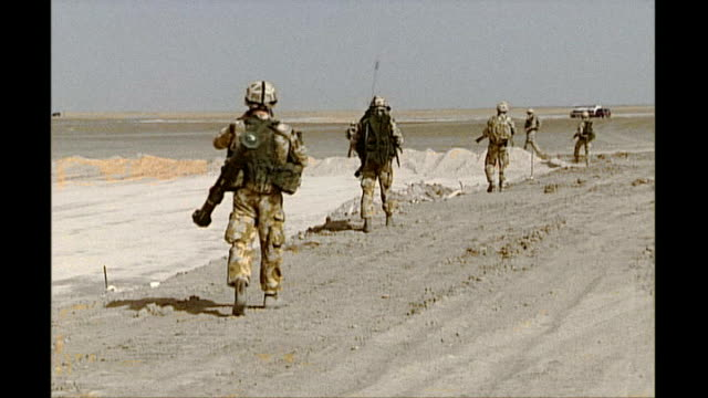 Report on British mission and whether it is succeeding Date Unknown Helmand Province MOTION shots of British soldiers patrolling in desert Back View...