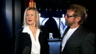 Reporter to camera Bjorn Ulvaeus and AnniFrid Lyngstad interview SOT CUTAWAYs poster of AnniFrid / Poster of Abba / White satin costumes and platform...