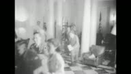 Reporters rushing through room in White House after President Harry Truman announces end of war / two women standing on ledge of building in Times...