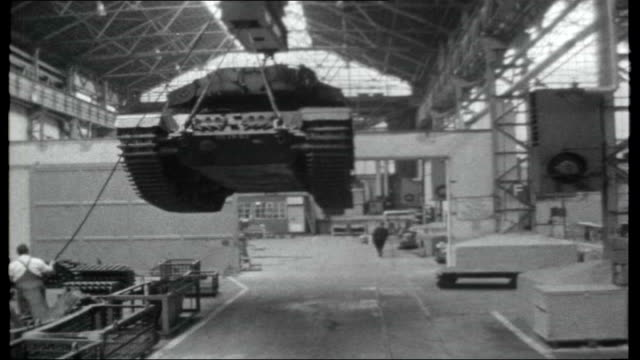 West Germany's role in NATO Various shots of factory workers producing goods for British army forces / Old army tank hoisted along through workshop...