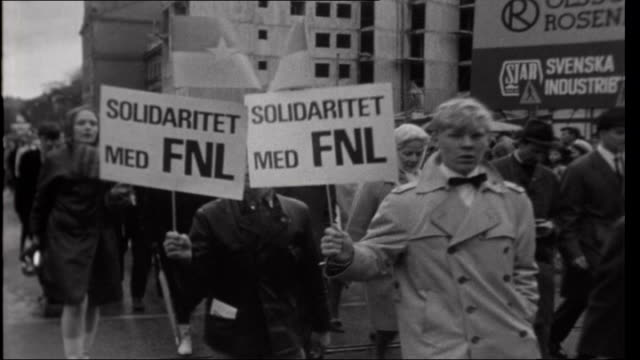 Russell Tribunal on US war crimes in Vietnam Students along protesting Protestors along Old man watching Banner carried along 'Americans in Sweden...