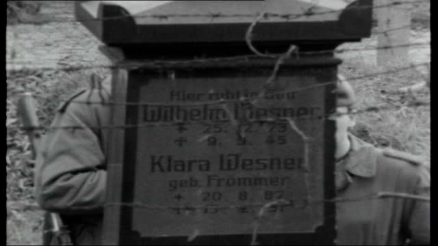 West Berlin East Berlin EXT Armed East German guards patrolling through cemetery and one walks up to gravestone marked 'Wilhem Wesner Clara Wesner'...