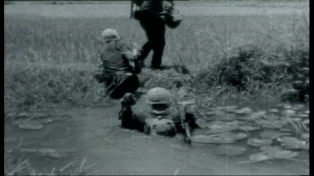 Vietnam US Marines in Da Nang Various shots of marines patrolling through countryside Marine drinking water from canister Marines wading waist high...