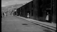 Wales coal miners absenteeism EXT Mechanical digger moving slag heap PAN along hillside at Maerdy Colliery Traffic along street Men boarding bus Row...