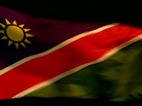 Republic of Namibia country flag flying against black BG Divided by diagonal strip of red lined w/ white upper triangle blue w/ yellow sunburst...