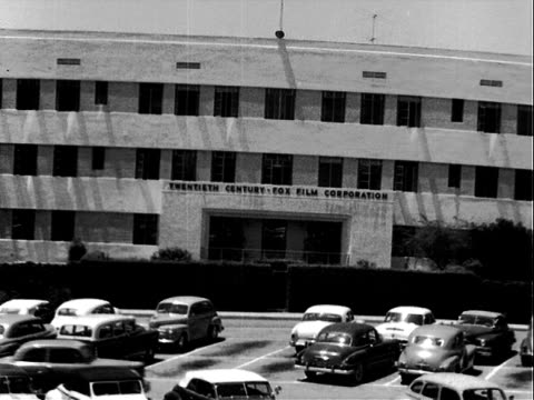 Republic Pictures studios offices mountains in background / Twentieth Century Fox Film Corporation office building cars parked in parking lot in...