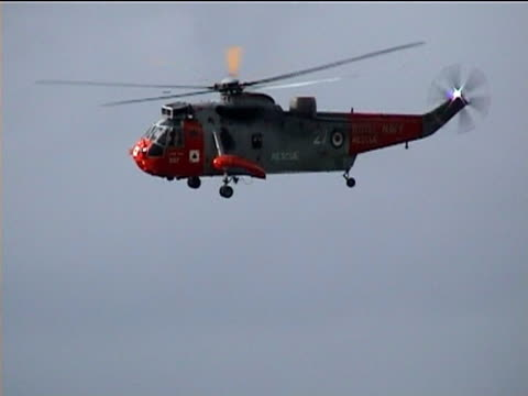 Rescue helicopter flies over rooftops of badly damaged area during flood Boscastle Cornwall 2004