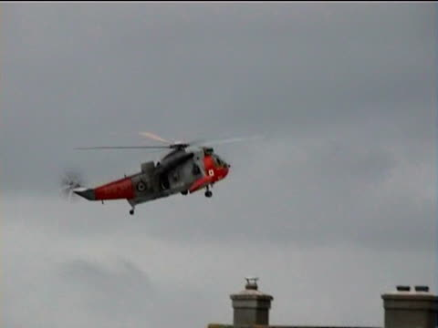 Rescue helicopter flies over village rooftops during floods Boscastle Cornwall 2004