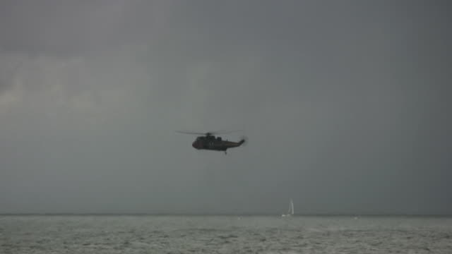 Rescue helicopter hovering over sea, passenger ship, HD