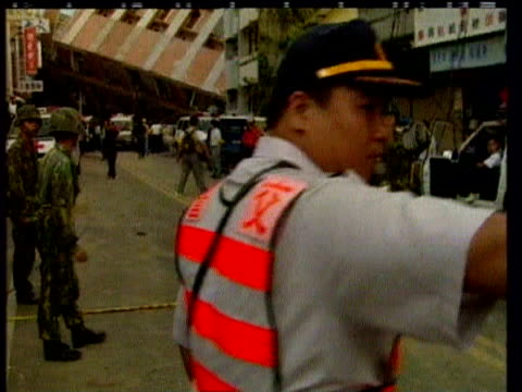Rescue servicemen and police evacuate people from collapsed building following earthquake Chi Chi Taiwan 23 September 1999