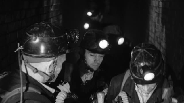 MONTAGE Rescue team with headlamps checking gas level in mine, hanging canary cage, putting on gas masks, checking and adjusting gauges, checking stopwatch, writing 'Fresh Air' on mine walls / England, United Kingdom