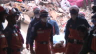 Rescue workers carry the body of an earthquake victim and pause to say prayers in the aftermath of an earthquake in China