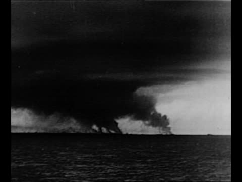 Rescued soldiers on ship / soldier in foreground watches from ship as smoke rises from fires on French shore after Allied evacuation during World War...
