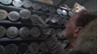 TS Researcher selecting and removing ice sample from racks of samples in metal tubes / Ohio, United States