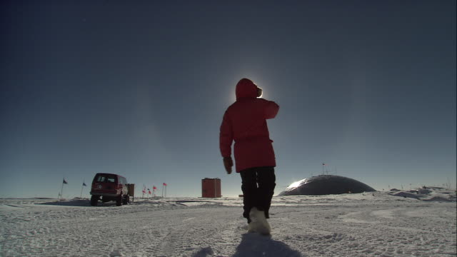 LA Researcher walks in the snow in front of dome / Antarctica