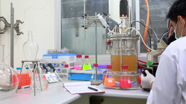 Researcher work with a microscope in laboratory.