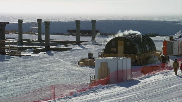 ZO Researchers walking in snow next to the Amundsen-Scott South Pole station / Antarctica