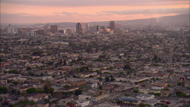 AERIAL Residential area with downtown buildings in background at sunset, Long Beach, California, USA