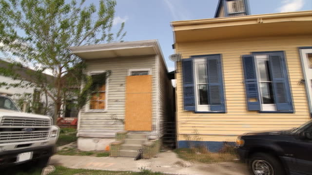 Residential neighborhood small houses boarded up damaged windows doors broken glass peeling paint small yards parked vehicles stop sign Low income...