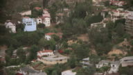 AERIAL Residential neighborhoods in the Basin, the Griffith Observatory, and the hillside of Mount Hollywood / Los Angeles, California, United States