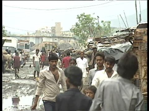 Residents walk along muddy road through Bombay slums Jul 1989
