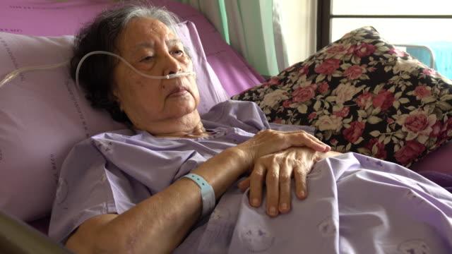 Respiratory oxygen nasal catheter to senior woman patient
