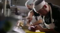Restaurant chef carefully cuts tuna steak on chopping block in busy kitchen restaurant