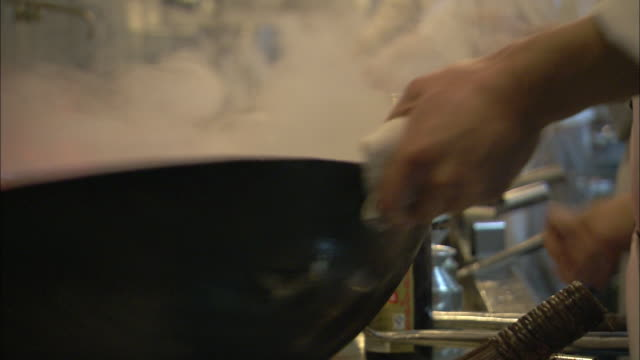 A restaurant chef spins a wok and adds ingredients.