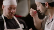 Restaurant chefs sample hot peppers, talk and laugh in kitchen restaurant