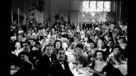 1945, restaurant, formally dressed people sitting at tables clapping