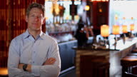 A restaurant owner stands with his arms folded near the bar.