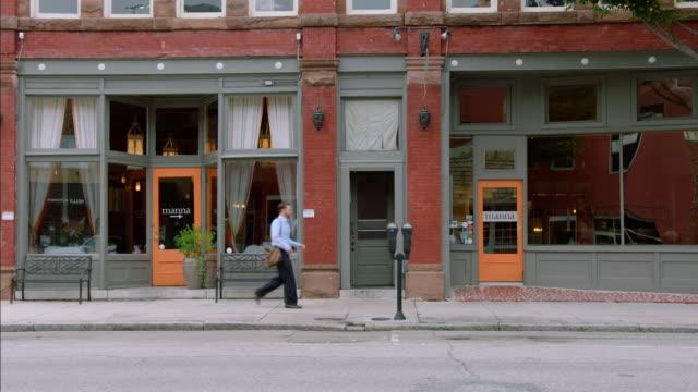 Restaurant owner walks down sidewalk and unlocks business storefront