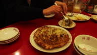 Restaurant patron cuts up chinese noodle pancake
