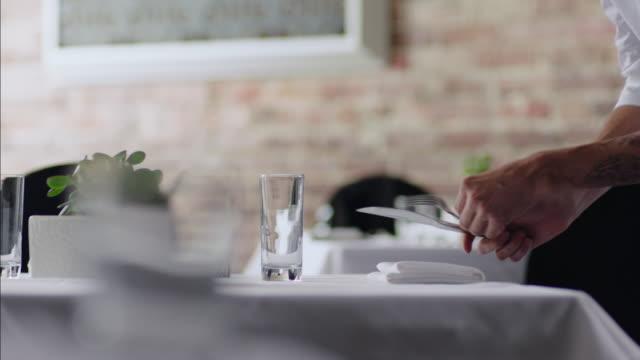 Restaurant waiter arranges silverware with precision