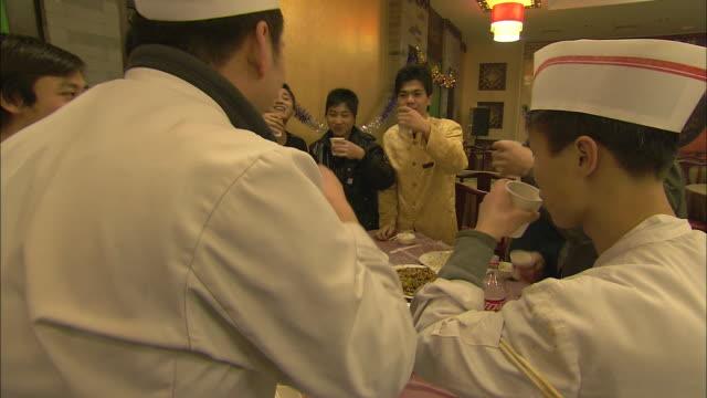 Restaurant workers drink a toast with Coca-Cola before sitting down to eat at a Chinese New Year party.