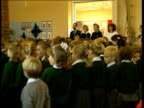 25% of seven year olds cannot read or do simple sums ENGLAND West Sussex Bishop Tufnell School BV Primary pupils stand in assembly as teachers in b/g...