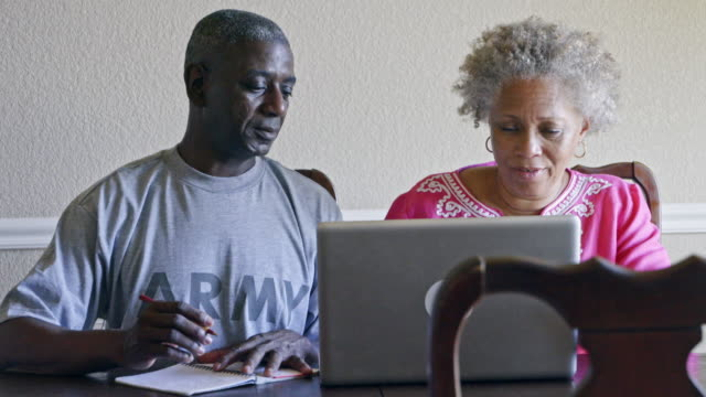 Retired Black military man and wife researching benefits on laptop