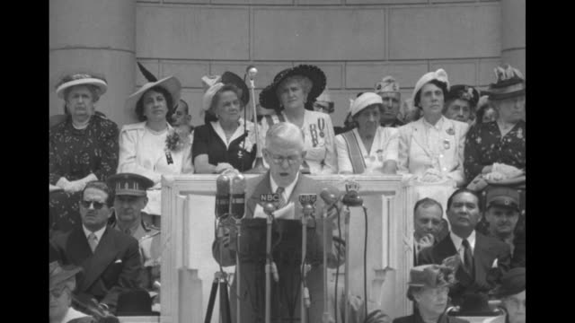 Retired Gen George Marshall on stage as those behind him stand and applaud then sit down / amphitheater stage with Marshall standing behind...