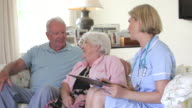 Retired Senior Couple Having Health Check With Nurse At Home