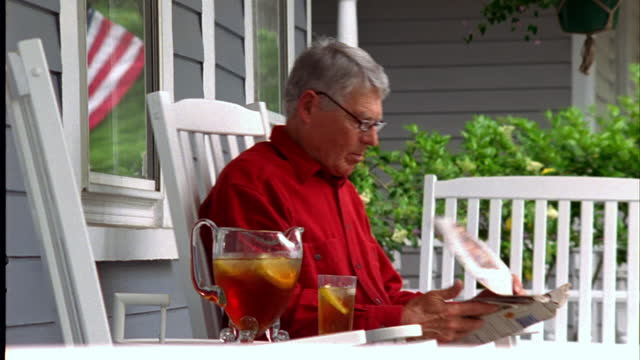 A retiree reads the newspaper on his front porch.