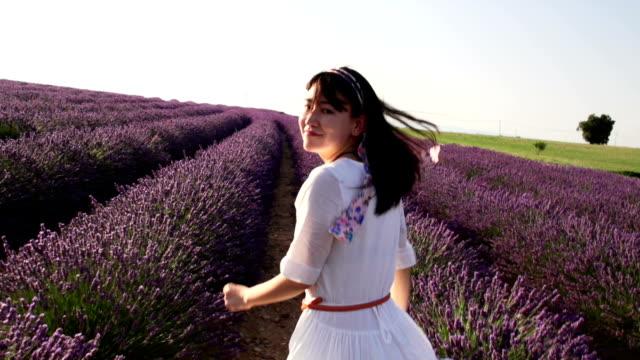 Sie mit Lächeln Gesicht beim Laufen in Lavendel Feld