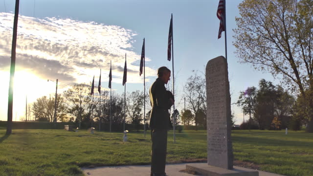 Returning military service man walks to a WWII monument in a cemetery in a small town.