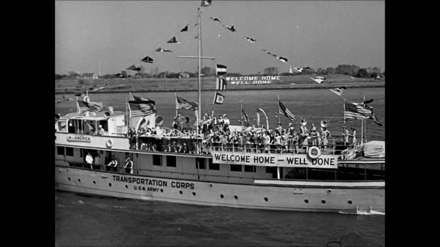 HD Returning US soldiers all over deck of transport ship waving excited Women on deck of boat w/ 'Welcome HomeWell Done' sign women excited throwing...