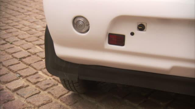 A Reva electric car sits on a cobblestone lot.