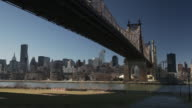 A reveal of the 59th Street Queensboro Bridge taken from Queens looking at Manhattan the East River is flowing below.