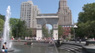 Reveal shot showing the Empire State Building and the Washington Square Park Arch with the water fountain in the foreground on a hot summer day in NYC