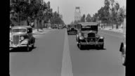 Reverse process plate shot from car moving down daytime Wilshire Boulevard passing car traffic / passing by Warner Bros Beverly Hills Theatre showing...
