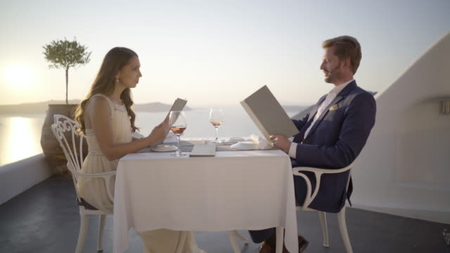 rich beautiful couple at romantic dinner outdoors in greece